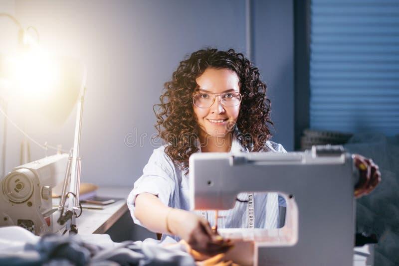 Abstimmende Nähmaschine der netten Damenschneiderin für Arbeit an beleuchtetem Studio stockfotos