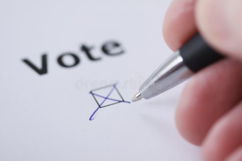 Abstimmungs- Hand des Mannes stellt Kennzeichen im Auswahlkästchen mit Stift ein - Hand, Wort und Stift absichtlich verwischt lizenzfreie stockfotos