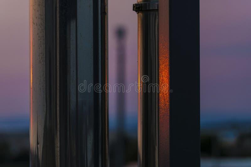 A abstração de um por do sol refletiu em duas colunas do metal foto de stock royalty free