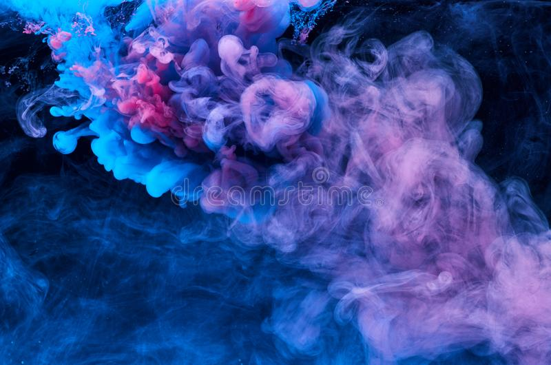 Abstract acrylic paint color swirls in water, shot from below, black background. Abstract background. Ink blot royalty free stock photo