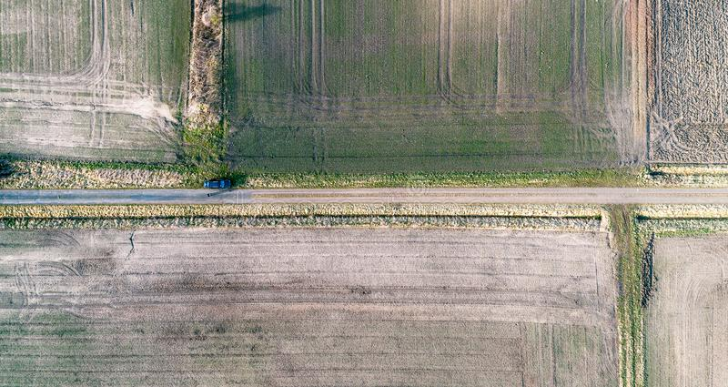 Abstract aerial view, vertical view of a straight dirt road between fields, black car on the way stock photo