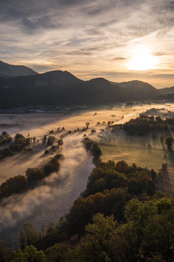 Abstract with Airuno on Adda river in Italy at sunrise with myst fog trees foliage in autumn fall season. Airuno on Adda river in Northern Italy at sunrise with stock image