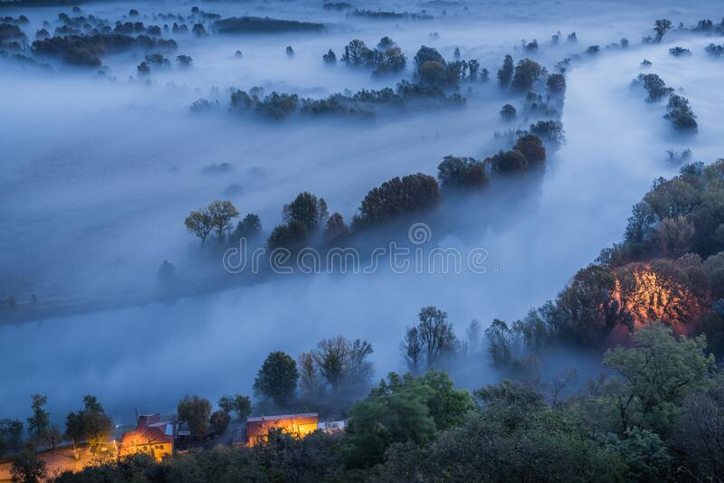 Abstract with Airuno on Adda river in Italy at sunrise with myst fog trees foliage in autumn fall season. Airuno on Adda river in Northern Italy at sunrise with royalty free stock photos