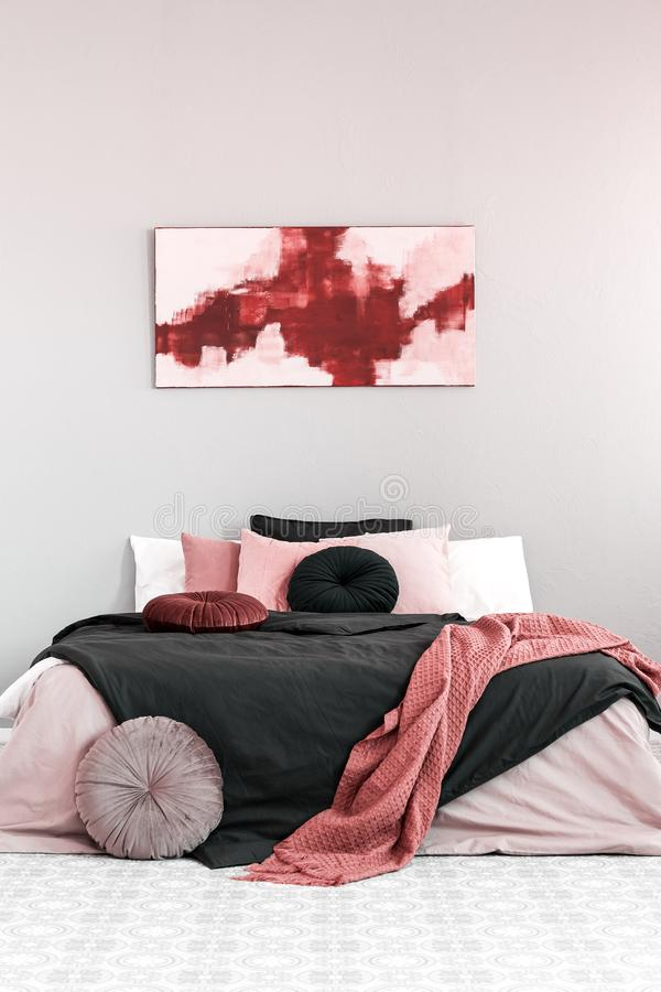 Abstract amaranth and pastel pink painting above king size bed with pink and black bedding royalty free stock photography