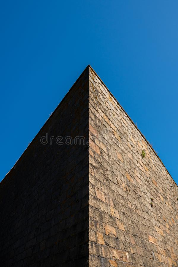 Abstract architecture outdoors. Sharp angle of an old massive stone wall  top corner with contrast dark shadow and bright side aga royalty free stock photography