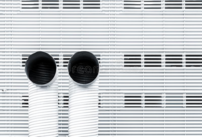 Abstract architecture picture with two ventilation pipes. Against striped metal facade royalty free stock photo