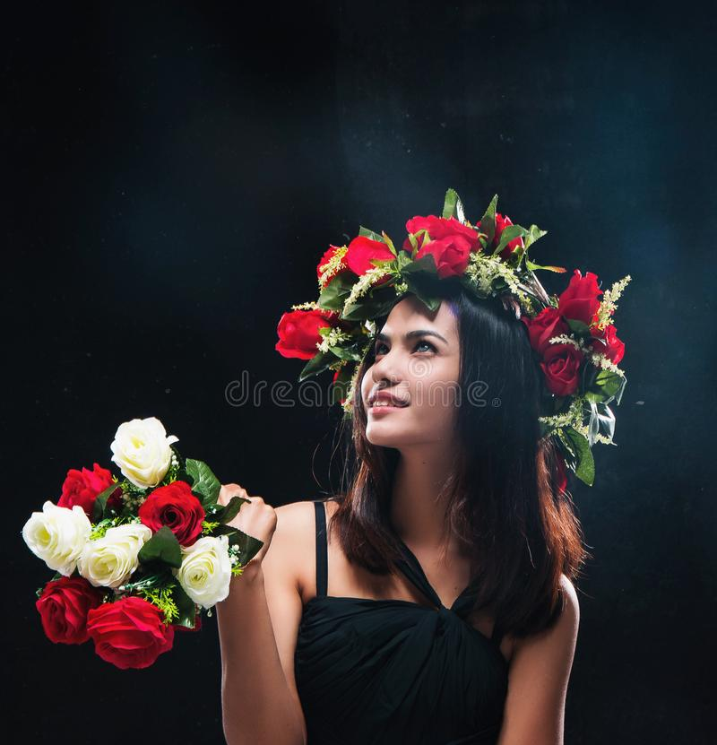 The abstract art design background of beauty lady in black dress with rose crown and rose bouquet,looking at the top left of backg royalty free stock photography