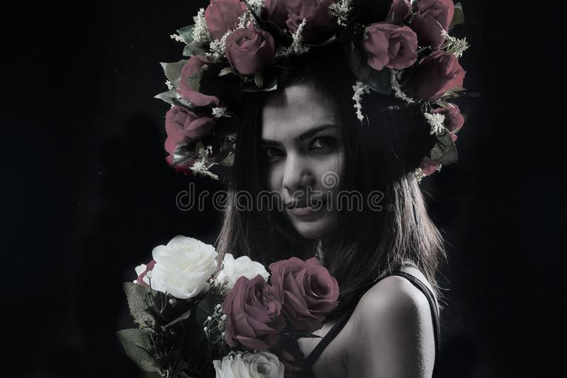 The abstract art design background of beauty lady in black dress with rose crown and rose bouquet,posing with smile and beautiful royalty free stock photography