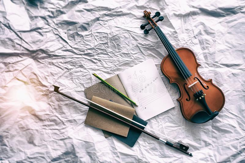 The abstract art design background of violin put beside the opened book and bow stock photos