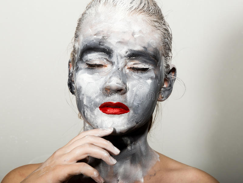 Abstract art makeup. Face and neck girls smeared with gray colors and bright red lips. Holi Festival stock images