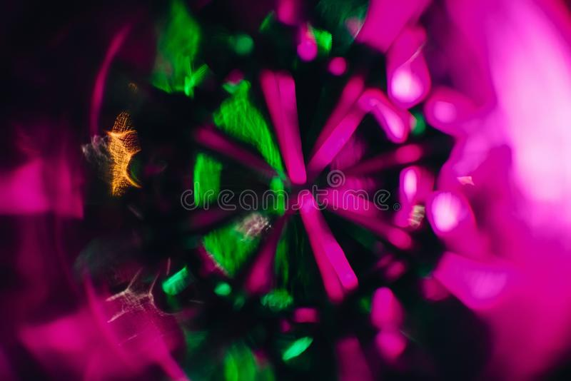 Abstract art texture photograph through the glass Cup with pink purple and green glow. To the background stock image