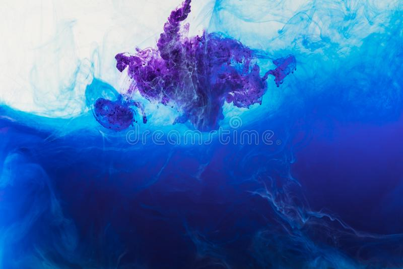 Abstract background with blue and purple paint flowing in water stock photo