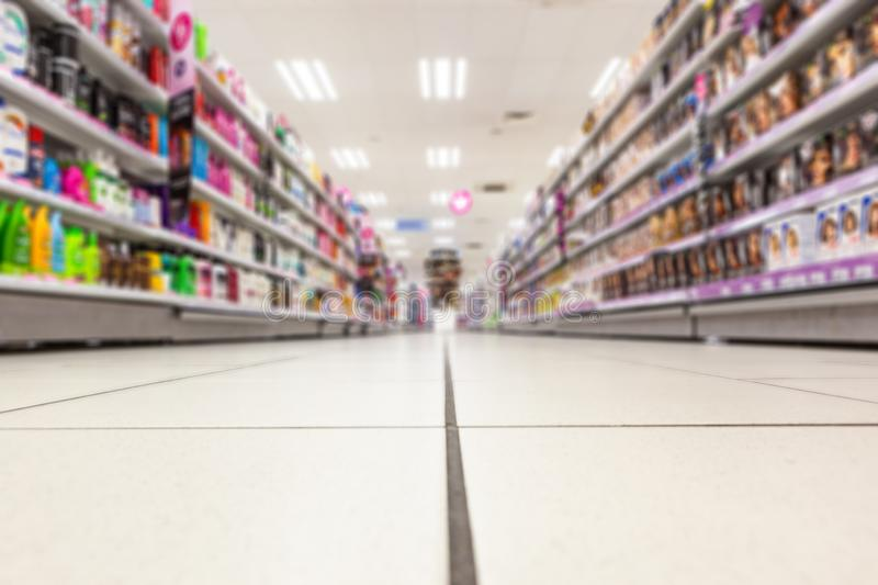 Abstract background blurred photograph of an aisle with shelves in bright modern drugstore at supermarket shopping center.  stock photo