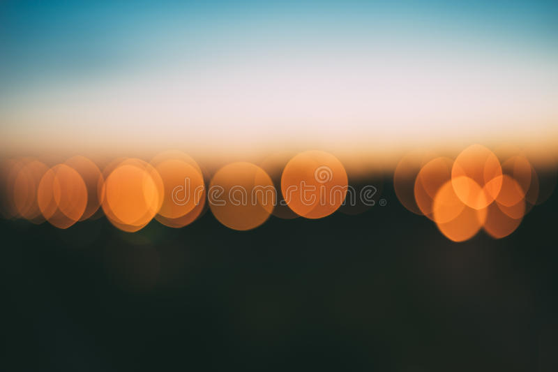 Abstract background of bright orange bokeh lights. With smooth defocused effect, blurred skyline after sunset royalty free stock photography