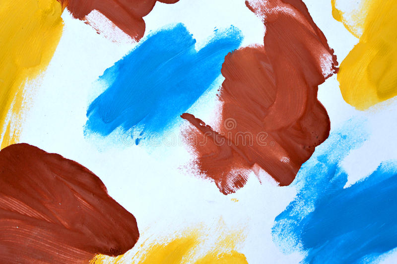 Abstract background brush strokes yellow, brown, blue ink white paper. Abstract background brush strokes yellow, brown, blue ink on white paper close-up stock photography