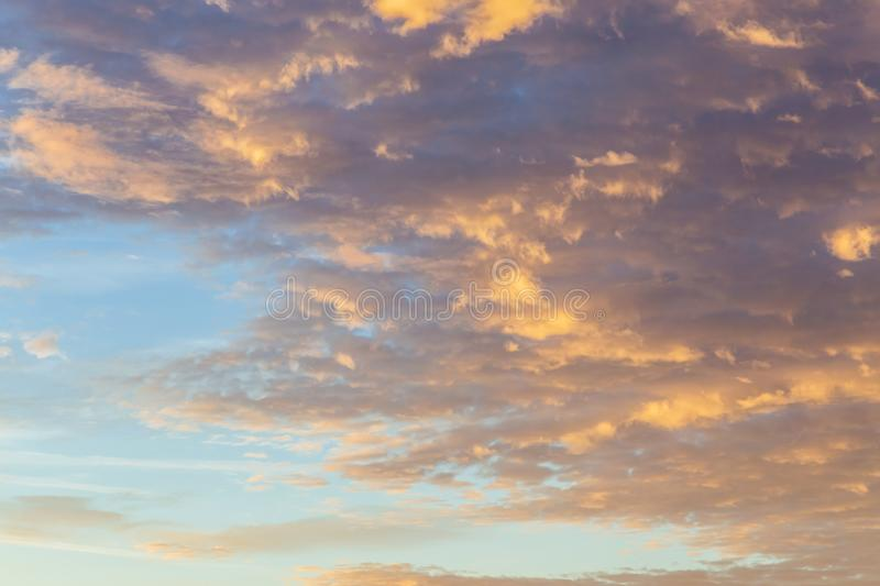 Abstract background with a cloud texture at sunset before a thunderstorm. Heavenly landscape. Beautiful morning blue sky painted stock photography