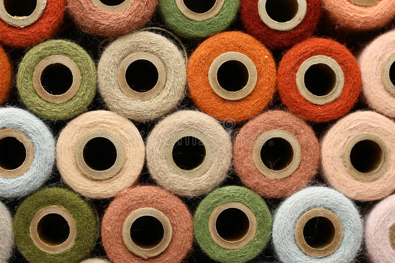 Abstract Background Collection of Antique Yarn Spools. An antique yarn spool collection is stacked together to create a colorful abstract circle background royalty free stock images
