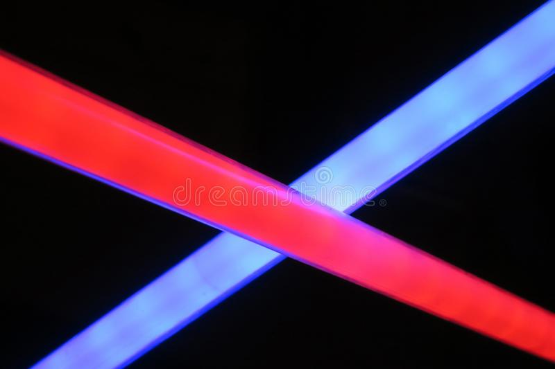 Red and blue light saber cross each other stock images