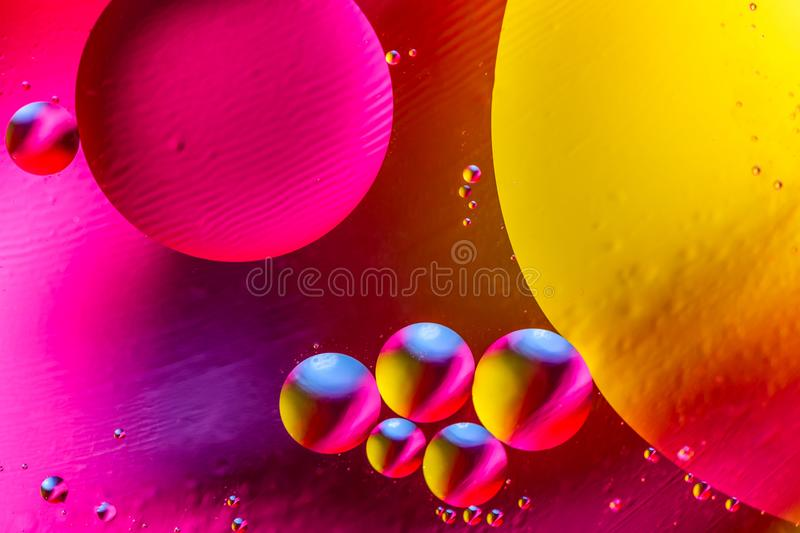 Abstract background with colorful gradient colors. Oil drops in water abstract psychedelic pattern image. Purple orange yellow col stock images