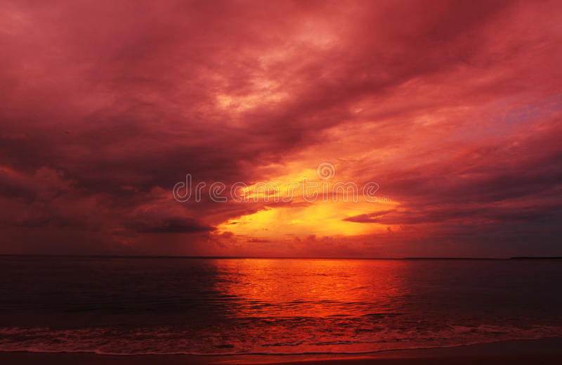 Abstract background colors fire in the sky summer sunset over sea. A stunning sunset over the sea resembles a ball of fire and flames in the sky with rich deep