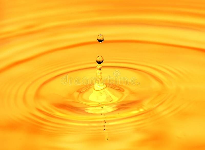 Abstract background. A drop of water falls in gold.  stock image