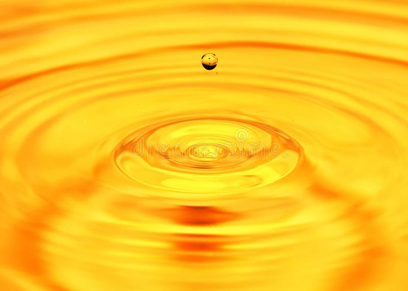 Abstract background. A drop of water falls in gold.  royalty free stock photography