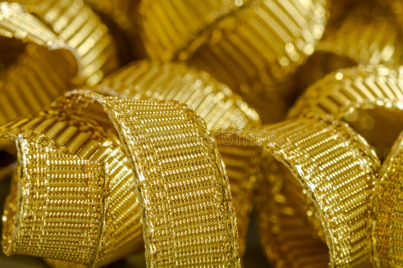 Abstract background of gold ribbon strands. Curls of gold ribbon close up stock photo