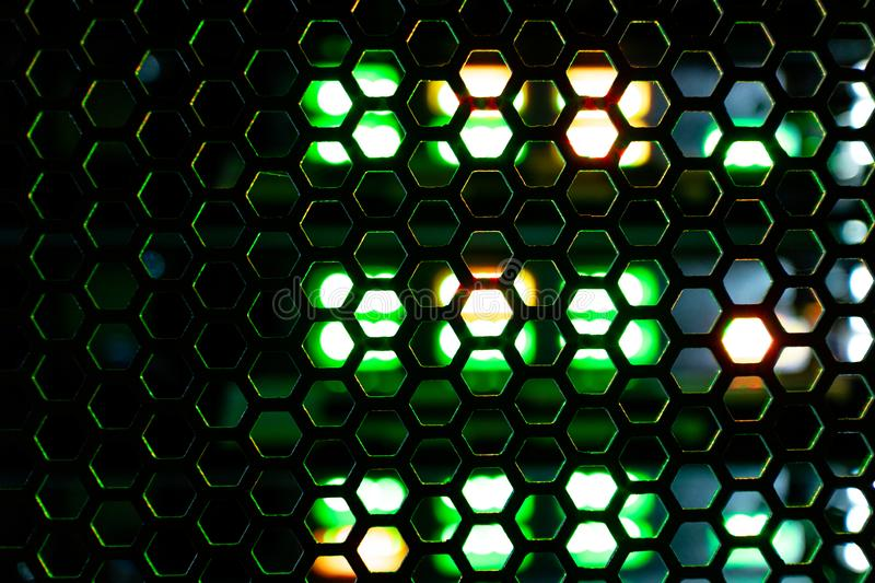 Abstract background grid consisting of hexagonal shapes behind which the green and orange light stock photos