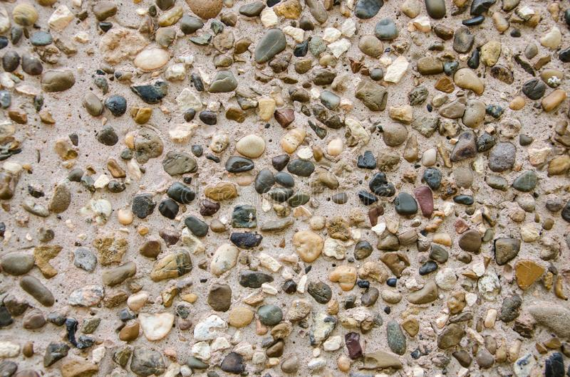 The abstract background. Many multi-colored small stones on the sand of the river. stock images