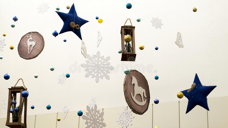 Christmas decorations and toys hang on thin threads: stars, snowflakes, lanterns, horse and deer. Abstract background of New Year. Abstract background of New royalty free stock photos