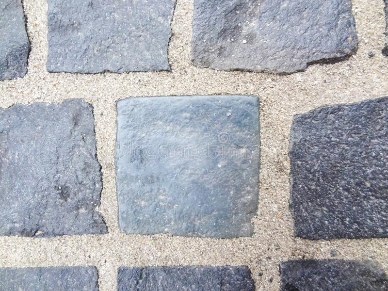 Abstract background of old cobblestone pavement up close. Stone texture of the pavement. Granite paving pavement background. stock photo