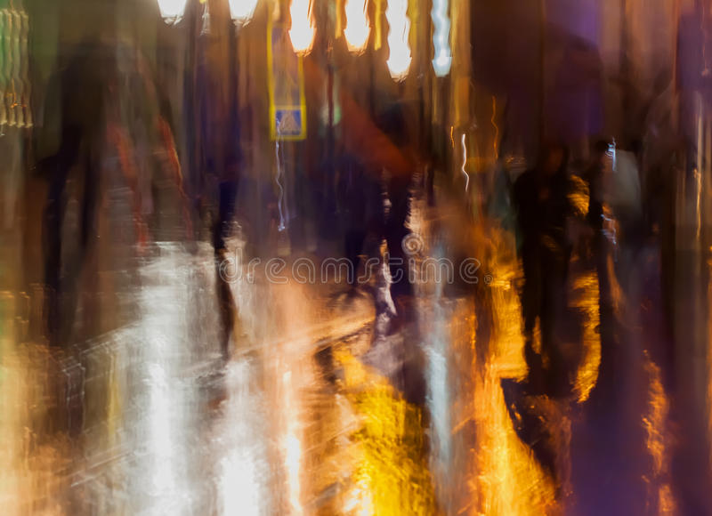 Abstract background of people figures, city street in rain, orange-brown tones. Intentional motion blur. Bright. Abstract background of blurred people figures royalty free stock photography