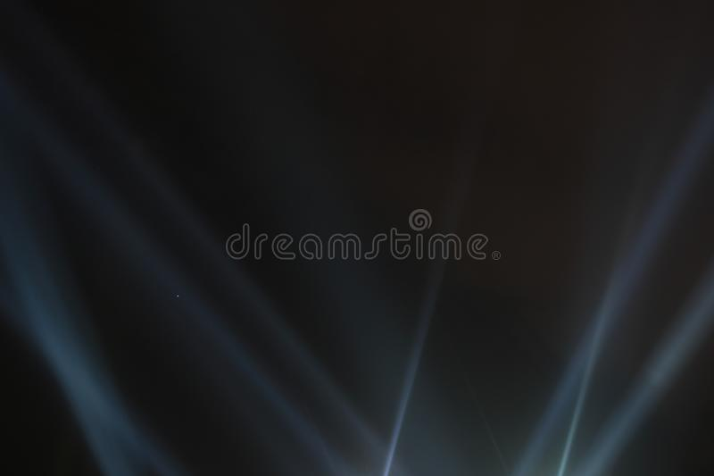 Searchlights shining beams of light into the black sky. royalty free stock photography
