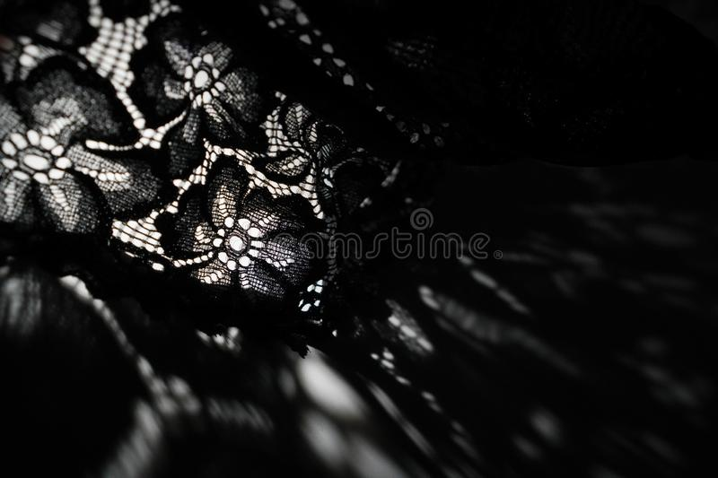 Abstract background of shadows black floral laces on white table. Light going through black lace. Romantic, passion background for. Sites, flyers, package royalty free stock photography