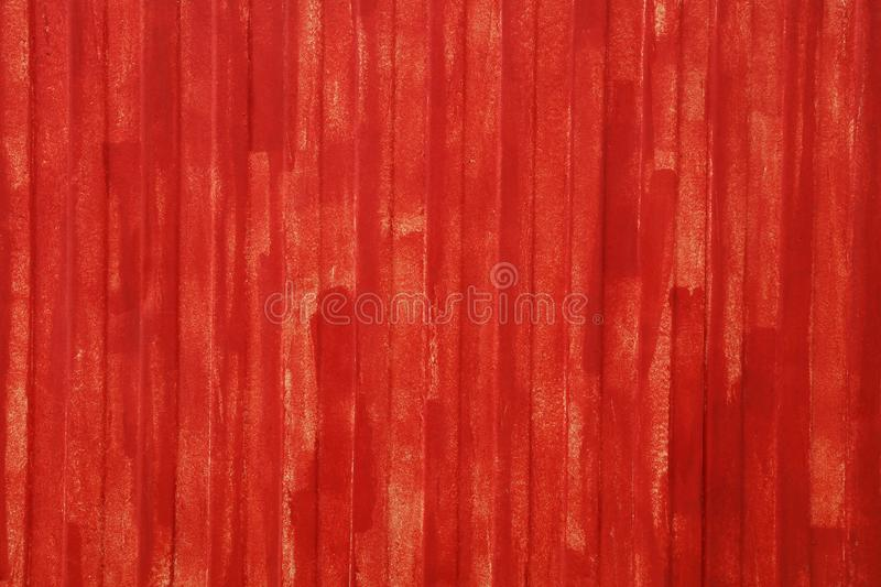 Red painted uneven metal wall surface close up. Abstract background texture of red painted vivid metal wall surface with uneven grunge paint strokes, close up stock photos