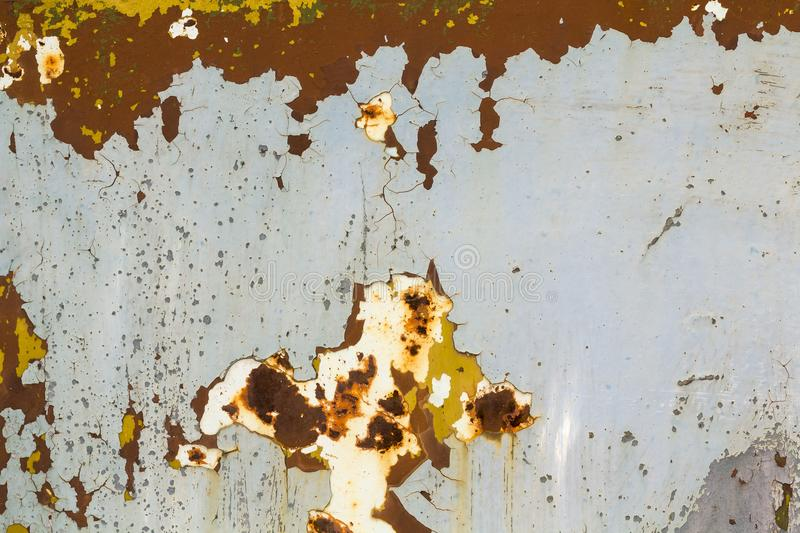 Abstract background texture of vertical grungy rusting metal plate with peeling paint and extensive corrosion with rust streaks. Abstract background texture of stock photo