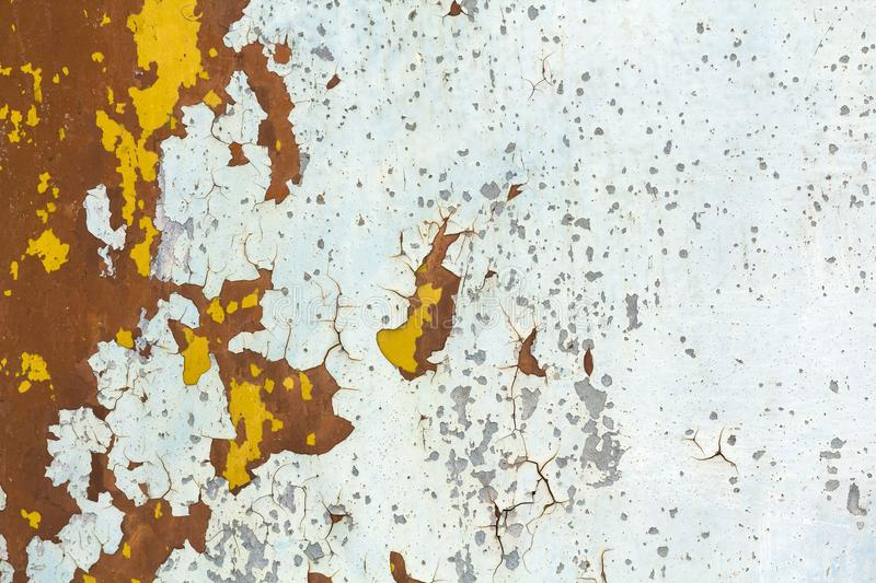 Abstract background texture of vertical grungy rusting metal plate with peeling paint and extensive corrosion with rust streaks. Abstract background texture of royalty free stock photo