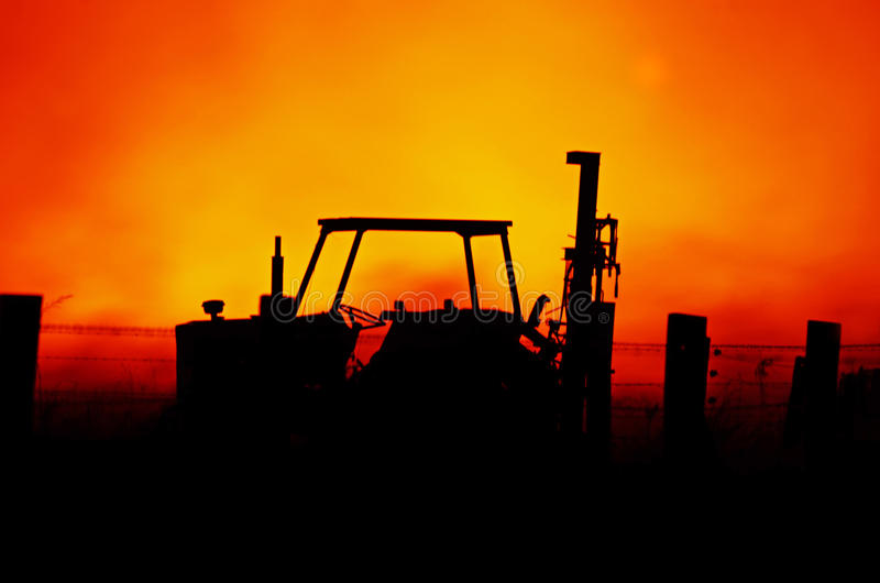 Abstract background tractor & farm fence with blazing Australian bushfire. An abstract background showing the silhouette image of a farm barb wire fence and stock photos