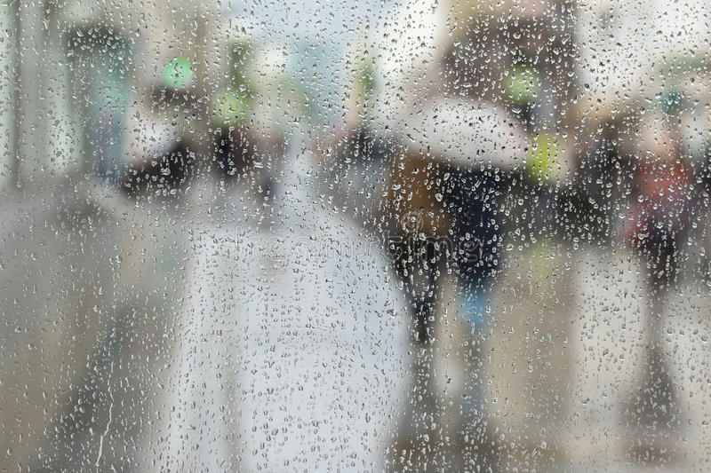 Abstract background of two young people under umbrella, walk on road in city in rain. Water drops on glass. Intentional royalty free stock image