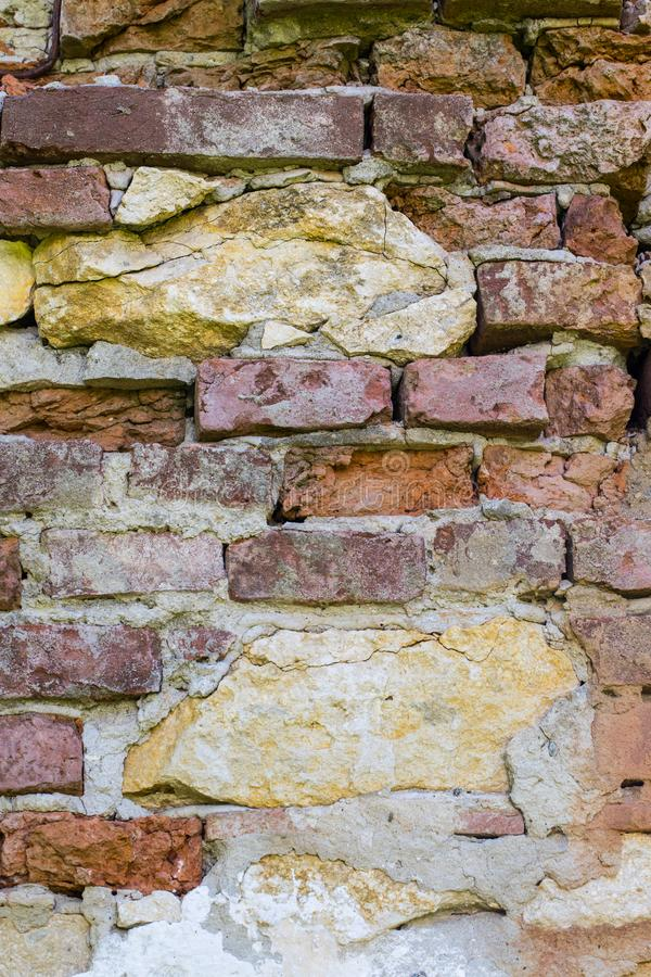 Abstract backgrounds: ancient ruined red brick wall with lime stones. Abstract backgrounds: ancient ruined red brick wall with yellow lime stones royalty free stock images