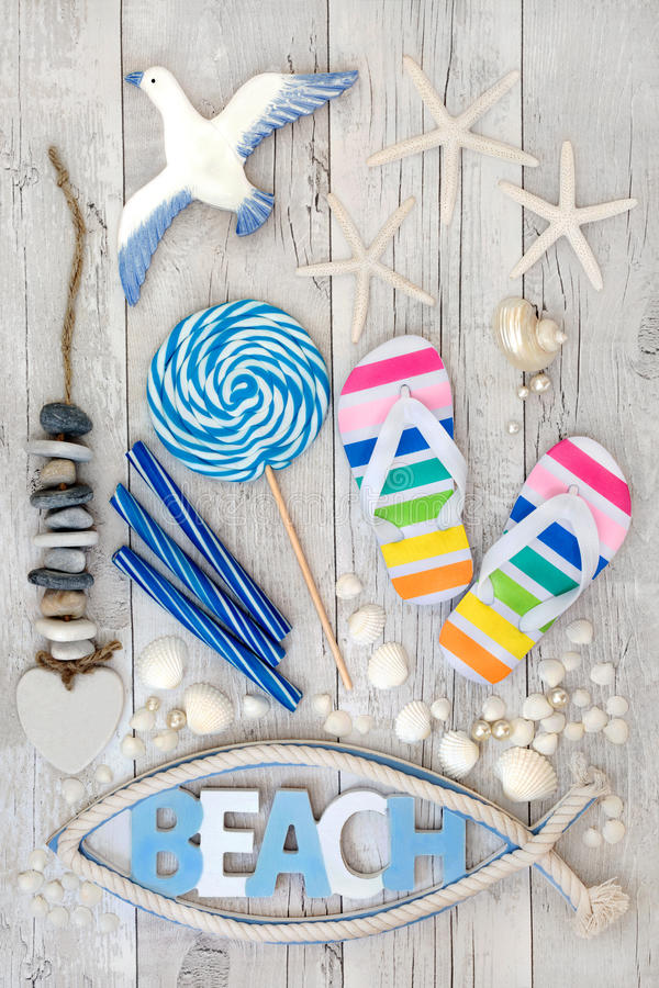 Abstract Beach Art. Collage with flip flops, candy rock, seashells, pearls and decorative seaside items on distressed white wood forming a background. Summer stock photography