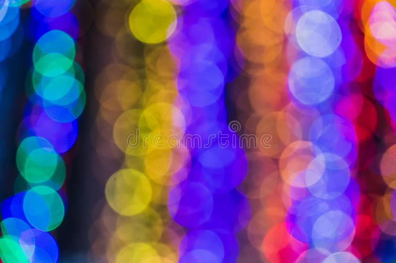 A blurred background with a group of multi colored blue, green, red circles from lighted lamps. The abstract beautiful blurred background with a group of multi royalty free stock image