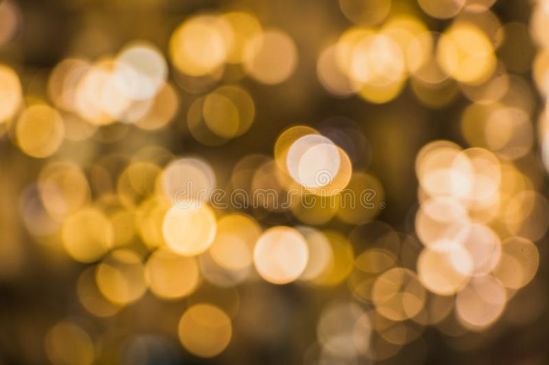 A blurred background with a group of yellow, orange, brown circles from lighted lamps. The abstract beautiful blurred background with a group of multi colored royalty free stock images