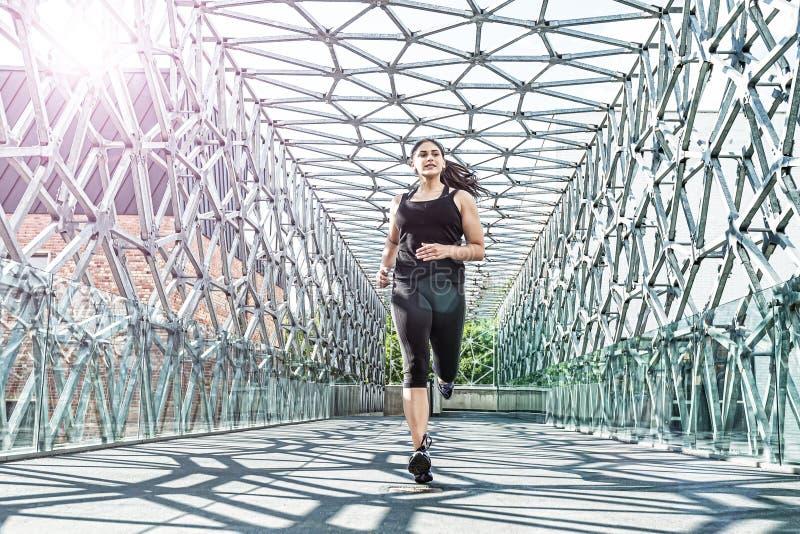 Abstract - Beautiful woman running on a modern metal bridge.  stock image