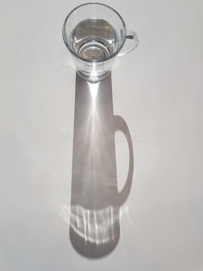 Abstract beeld van zonlicht dat door glas water schijnt, dat een heldere straal van licht en schaduw, hydratatiethema creëert royalty-vrije stock fotografie