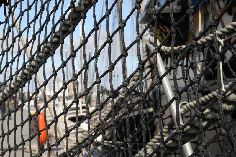 Abstract black netting on old clipper ship in harbour. Netting in focus with harbour beyond royalty free stock photos