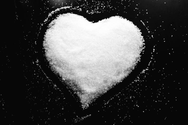 Abstract black and white photo in retro style with image of heart made of white sugar on black background royalty free stock image