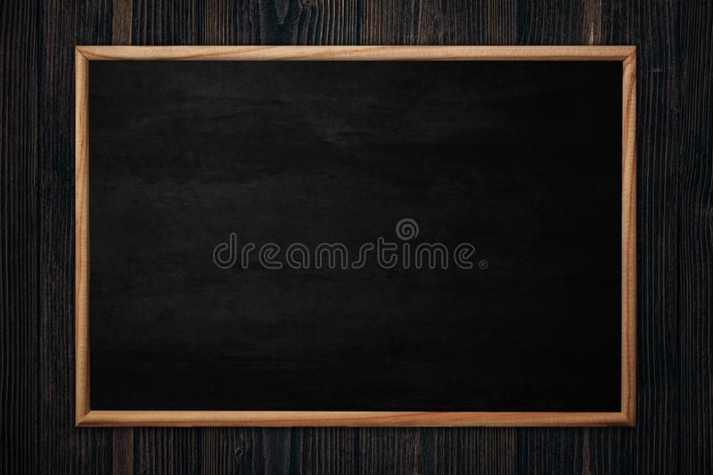 Abstract blackboard or chalkboard with frame on wooden background royalty free stock image