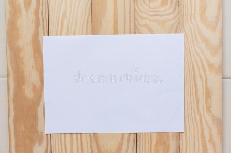 Abstract Blank one white paper on wooden table top view background concept for empty letter business sheet, plain brochure mock up. Template, flyer card royalty free stock image