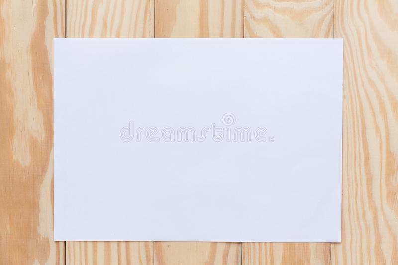 Abstract Blank one white paper on wooden table top view background concept for empty letter business sheet, plain brochure mock up. Template, flyer card stock image
